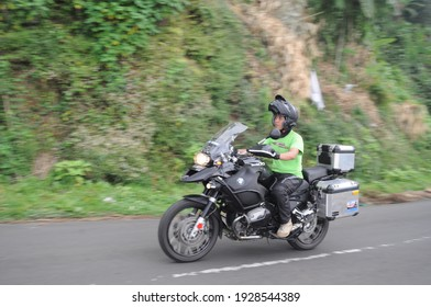 The panning technique of the motorcyclist who is about to work is in a hurry at full speed: Malang, Indonesia - January 28, 2021