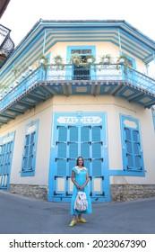 PANO LEFKARA, CYPRUS - AUGUST 5, 2021: Russian tourist woman in Pano Lefkara village, Cyprus. Architectural fashion. Retro look with collar, dress. Street style, trendy outfit. Pano Lefkara landmark