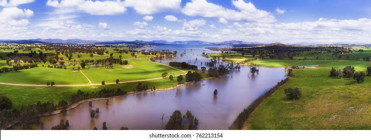 Panorama above Murray river flowing through Hume Lake in regional rural NSW surrounded by green cultivated agricultural fiels of farms.