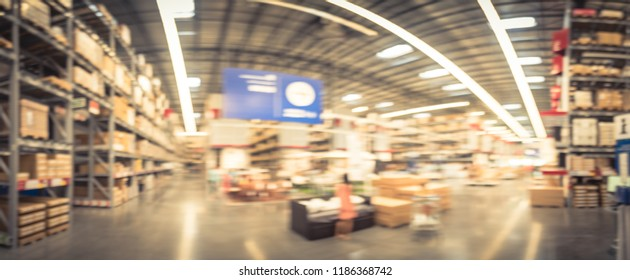 Panorama abstract blurred large furniture warehouse in Texas, America with customer shopping. Defocused industrial storehouse interior full of boxes, row of aisles, bins, shelves from floor to ceiling