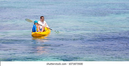 panorama of active family of two, father and son, enjoying kayaking together, tropical vacation concept, copy space on right