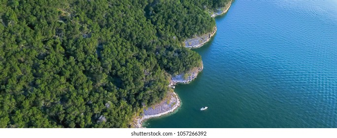 Panorama  aerial bluffs with small boat at Lake Travis, Austin, Texas, USA. Trees, cliff rock wall coming out of water from above. Blue ocean crystal, moderate wave looking straight down, green forest