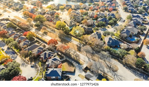 Panorama aerial drone view lakeside residential neighborhood in North of Dallas, Texas, USA during fall season. Row of single-family houses subdivision with colorful autumn leaves