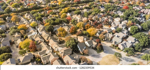 Panorama aerial drone view urban sprawl in suburban Dallas, Texas during fall season with colorful leaves. Flyover subdivision with row of single-family detached houses and apartment complex