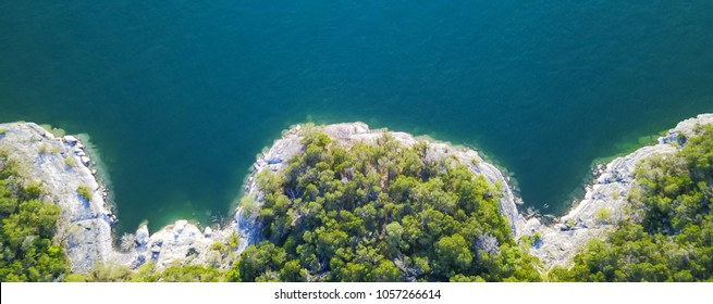 Panorama aerial view bluffs at Lake Travis, Austin, Texas, USA. Trees and cliff rock wall coming out of water from above. Blue ocean crystal, moderate waves looking straight down, green forest