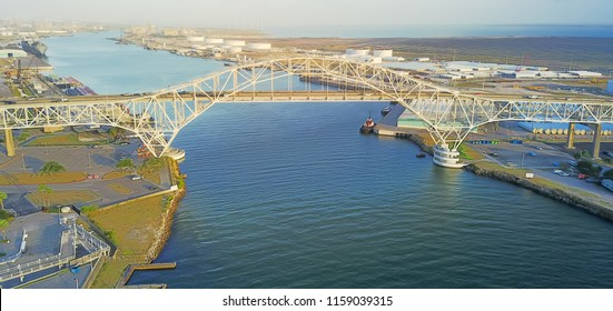 Panorama aerial view of Corpus Christi Harbor Bridge with row of oil tanks and wind turbines farm in distance. A through arch bridge crosses the Corpus Christi Ship Channel