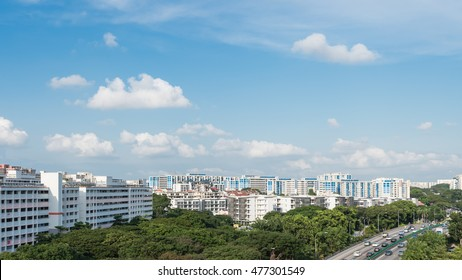 Panorama aerial view HDB housing complex near highway with green trees and vehicles in traffic. Cloud blue sky. Singapore is an excellent green, clean city. Asia transportation and infrastructure.