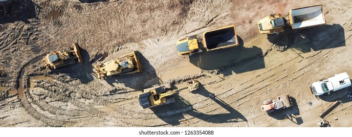 Panorama aerial view machinery and heavy-duty equipments at large construction site in Carrollton, Texas, USA. Top of excavator, bulldozer, dump truck, digger