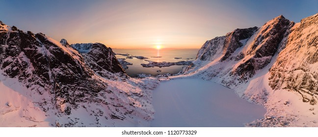 Panorama aerial view of mountain range with ice lake in valley with arctic ocean at sunset. Reine, Lofoten islands, Norway
