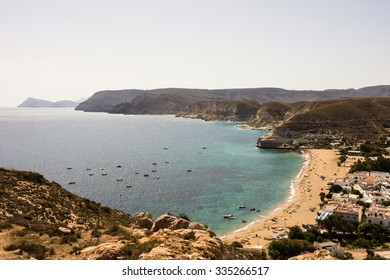 Panorama of Agua Amarga village in Cabo de Gata Nijar Natural Park, Almeria, Andalusia, Spain. View from the hill. White village by the sea, cliffs, popular resort with nice beach and clean water.