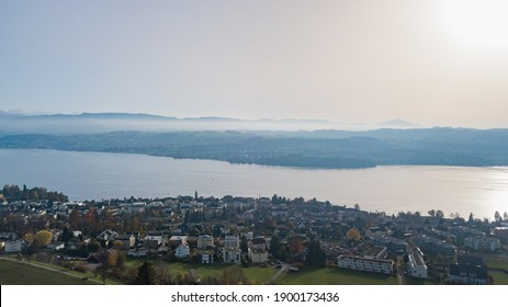 Panorama from the air of a village with Lake Zurich