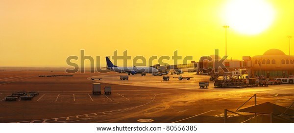 Panorama of an airport with plane near gate and part of a terminal at sunset light