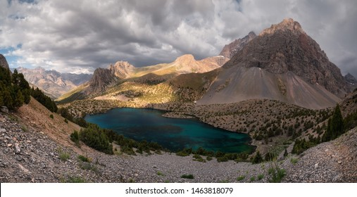 Panorama of Alaudinskoe Lake in the Fan Mountains. Turquoise water in the lake surrounded by mountain peaks, the best place on the planet for hiking