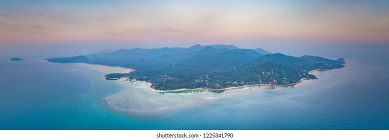 Panorama alone standing island. Sunset aerial drone shot. Ko Pha-ngan. Thailand. Overwhelmed view from above Ko Pha-ngan island and the ocean at the colorful sunset sky. The Kingdom of Thailand