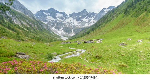 Panorama with alpine huts a mountain stream and glacier in the background