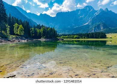 panorama of the alpine lake of Lake Fusine in Italy with transparent waters surrounded by forests of firs and rocky mountains