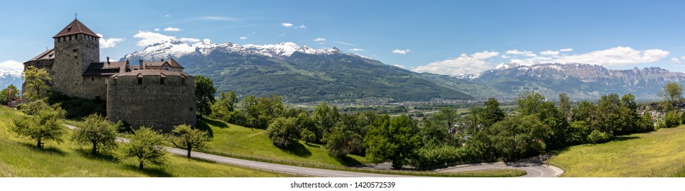 Panorama of an alpine landscape with high mountains and castle, green meadows and trees in spring with snow in the Liechtensteiner and Swiss Alps