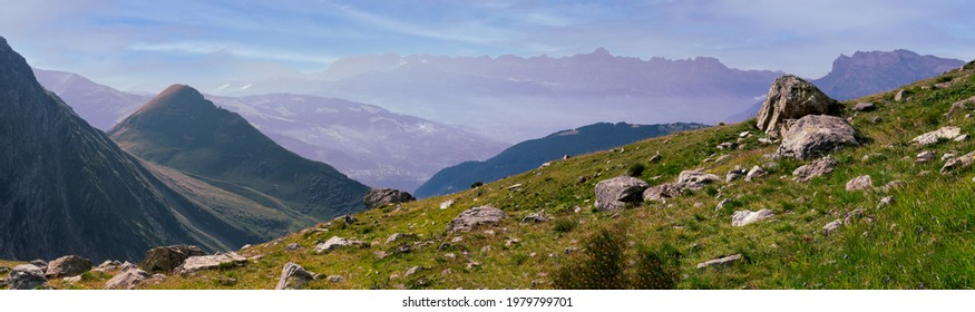 Panorama of the Alpine mountains. Ridges and peaks are visible in the background. Large and small stones lie on the grassy slope.