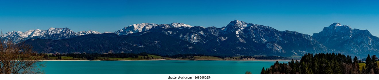 """Panorama of the  Ammergauer mountains from the """"Saeuling"""" till the """"Grosse Klammspitze"""" with snow-capped summits, deep blue sky and the barrier lake """"Forggensee"""" in the foreground"""