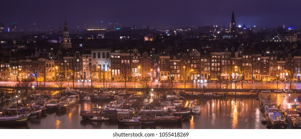 Panorama of Amsterdam city from up high at night with lights reflected in a nearby canal