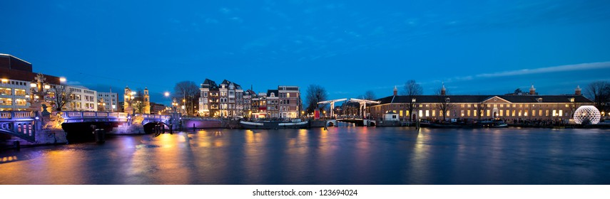 "Panorama of Amsterdam skyline at night, showing the ""skinny bridge"" and the museum Hermitage along the river Amstel"
