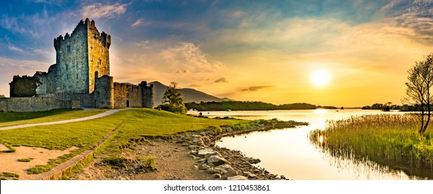 Panorama of ancient Ross Castle ruins with grass during sunset golden orange sky hour nobody