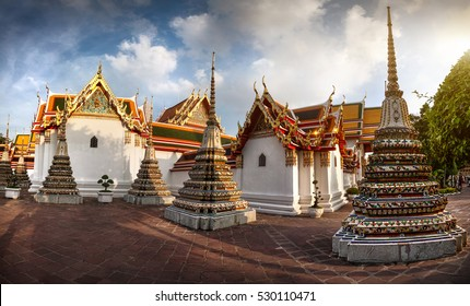 Panorama of Ancient Stupas and pagoda in Wat Pho temple in Bangkok at sunset