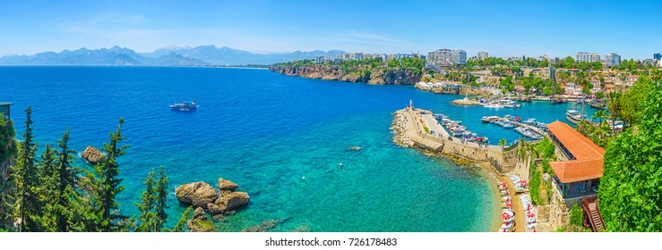 Panorama of Antalya coast from the tall cliff with Mermerli beach, Pier of old port, modern hotels and Taurus mountains on background, Turkey.