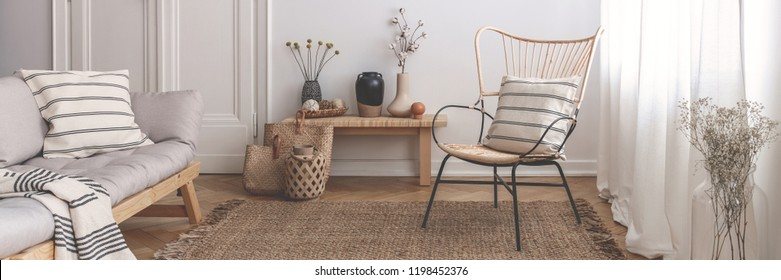 Panorama of armchair and grey sofa in natural living room interior with flowers. Real photo