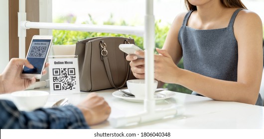 Panorama Asian customers scan QR code online menu. Customers sat on social distancing table for new normal lifestyle in restaurant after coronavirus covid-19 pandemic.