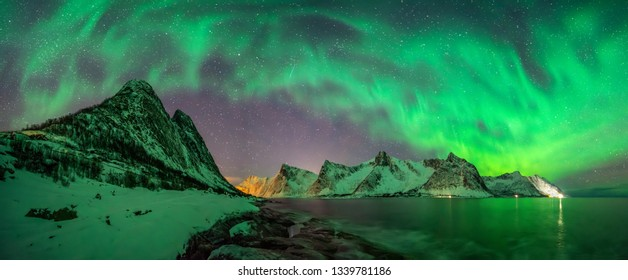 Panorama of Aurora over Tugeneset rocky coast with Kliptinden mountains in background, Senja,, Norway