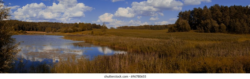 Panorama of autumn landscape, lake, forest and blue sky with clouds
