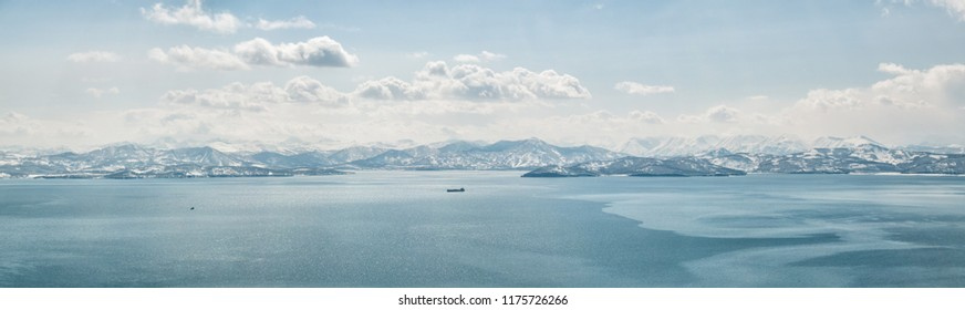 Panorama of Avacha Bay covered with thin ice in Petropavlovsk-Kamchatsky and view of snow-covered hills and volcanoes in winter on a clear day