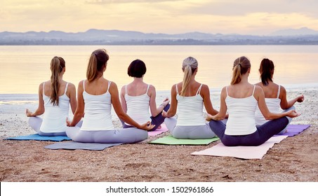 Panorama back view women group in activewear sitting in lotus position meditating do Siddhasana on sandy beach near sea feels placidity, stress relief balance harmony healthy lifestyle concept