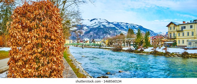 Panorama of Bad Ischl with dried plants in winter Sissi park, azure waters of Traun river, buildings of old town, Austria