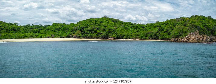 Panorama of Bahia Riscalillo beach coastline shoreline at Huatulco National Park in Oaxaca, view from the Pacific Ocean. Travel in Mexico. Background.