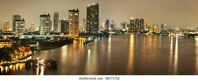 Panorama of Bangkok at night The capital of Thailand, one of the colourful cities in Asia. Hotel Lighting and Skyline Building Shines on the river Water traffic is full of tourist boats.
