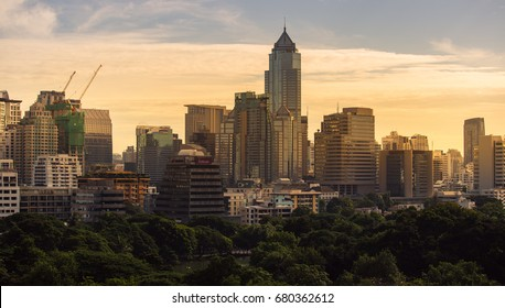 Panorama of Bangkok skyline with forest at sunset, Thailand.