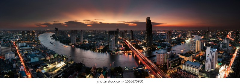 Panorama of Bangkok skyline and skyscraper over Chao Phraya River at sunset.