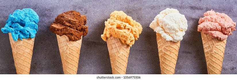 Panorama banner with assorted different flavors of artisanal ice-cream served in sugar cones in a row on a slate background