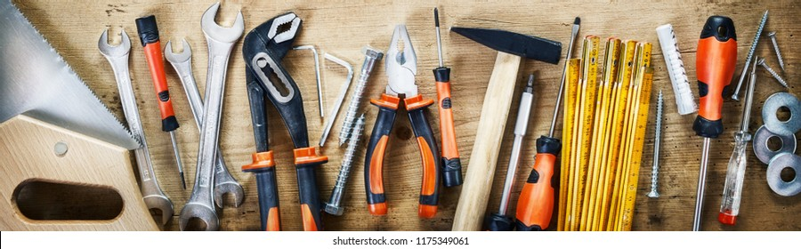 Panorama banner of assorted hand tools on wood for renovations, DIY, building and construction or woodworking