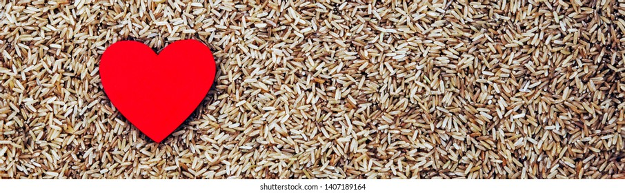 Panorama / banner - food concept for healthy wholemeal rice, with a healthy heart, for rice recipes, diet, cooking and loving rice - with design space.