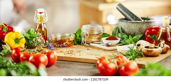 Panorama banner with fresh culinary herbs and spices on a chopping board with a pestle and mortar surrounded by fresh vegetables for salads