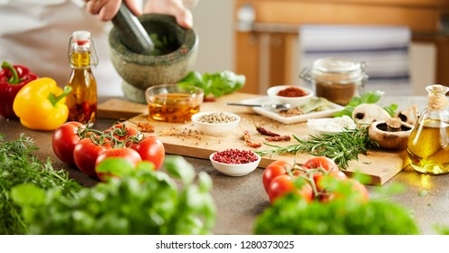 Panorama banner of the hands of a chef preparing herbs by blending them in a pestle and mortar with assorted spices and fresh vegetables on a wooden board