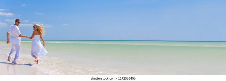 Panorama banner happy young man and woman couple running, laughing and holding hands on a deserted tropical beach with bright clear blue sky