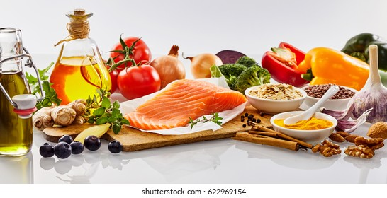 Panorama banner with healthy heart food with nuts, herbs, salmon, spices, bell peppers, tomatoes, broccoli, garlic, olive oil and blueberries on a white reflective backgeound