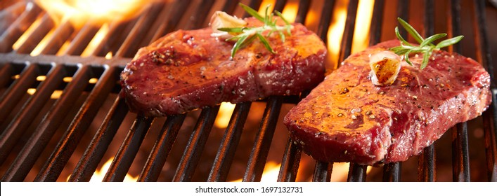 Panorama banner with raw beef steak on a BBQ grill sizzling over flaming hot coals in a close up view with copy space