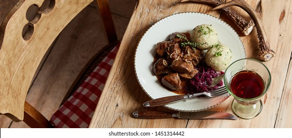 Panorama banner with speciality wild venison goulash served with dumplings and red cabbage on a rustic table set with red wine and deer antlers in a high angle view