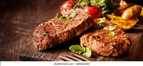 Panorama banner with succulent medallions of beef fillet steak seasoned and garnished with herbs on an old rustic wooden board with copy space