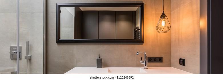 Panorama of bathroom with modern metal lamp and big mirror over basin